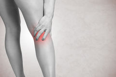 Pain in the Leg. Female jogger with pain in her lower leg, black and white,  in grey Stock Photography