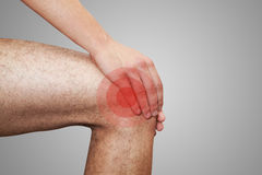 Pain in leg. The young man keeps for leg. On a grey background Royalty Free Stock Images