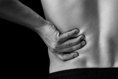 Pain in the lower back, close-up Stock Image