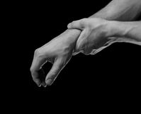 Pain in male wrist. Man holds his hand, acute pain in a wrist, black and white image Royalty Free Stock Photo