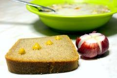 Pain, moutarde, oignons, un bol de soupe Images stock