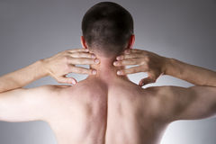 Pain in the neck. Man with backache. Pain in the man's body. On a gray background Stock Photos