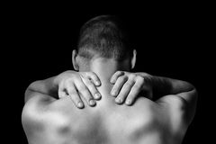 Pain in the neck. Unrecognizable man touches neck, pain in the neck, rear view stock photo