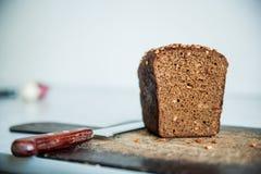 pain noir avec des graines de tournesol sur la planche à découper Photographie stock