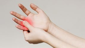 Pain and numbness in fingertips and palms. Woman massaging her sore hand, panorama stock image