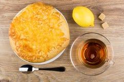 Pain plat avec du fromage en plat, thé, citron et sucre Image stock