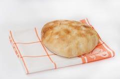 Pain plat domestique chaud sur un tissu de cuisine Images libres de droits