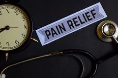 Pain Relief on the paper with Healthcare Concept Inspiration. alarm clock, Black stethoscope. stock photography