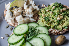 Pain rond de sarrasin ou de seigle avec le guacamole, le concombre et les poissons avec le tahini Images libres de droits