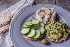 Pain rond de sarrasin ou de seigle avec le guacamole, le concombre et les poissons avec le tahini Photographie stock libre de droits