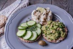 Pain rond de sarrasin ou de seigle avec le guacamole, le concombre et les poissons avec le tahini Photographie stock