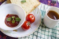 Pain sain de tomates de légumes crus avec la tasse de thé Image stock