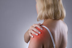 Pain in shoulder, care of female hands, ache in woman`s body royalty free stock images