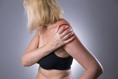Pain in shoulder, care of female hands, ache in woman`s body stock photos