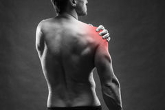 Pain in the shoulder. Muscular male body. Handsome bodybuilder posing on gray background. Black and white photo with red dot royalty free stock images