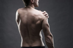 Pain in the shoulder. Muscular male body. Handsome bodybuilder posing on gray background. Low key close up studio shot Stock Images