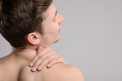 Pain in shoulder. Rear view of young shirtless man touching his shoulder by hand and keeping eyes closed while standing isolated on grey Royalty Free Stock Images