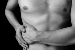 Pain in the side of the abdomen. Man holds on the right side of the abdomen, concept of pain Royalty Free Stock Image