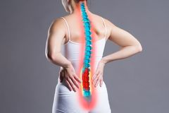 Pain in the spine, woman with backache on gray background, back injury. Photo with highlighted skeleton royalty free stock image