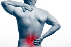 Pain in the spine. Young bald man sports physique holds a sick back on a white isolated background. Fracture of spine royalty free stock photos