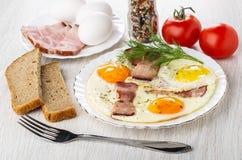 Pain, tomates, condiment, oeufs au plat avec la poitrine et aneth dans le plat, fourchette sur la table images libres de droits