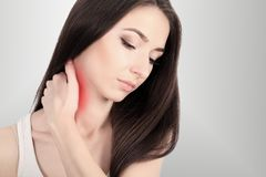 Pain A woman with a painful neck of the shoulder, painted red, highlighted on a gray wall of the background. Young beautiful woman. Irritation Traumatologist stock image