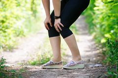 Pain in woman`s knee, massage of female leg, injury while running, trauma during workout. Outdoors concept stock images
