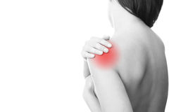 Pain in the womens shoulder. Hands on a womans shoulder. Pain in the muscles Royalty Free Stock Image
