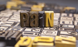 Pain  in wooden typeset. The word Pain surrounded by random typeset Stock Image