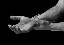 Pain in wrist area. Acute pain in a male wrist. Man holds his hand, black and white image Stock Images