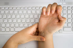 Pain on the wrist. Worker with pain on the wrist by the hard work at the office stock image