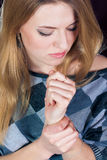 In Pain young woman holding her arm wrist Stock Photography