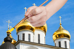 Painbrush paints golden cupola on russian church Royalty Free Stock Images