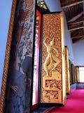 Painel de madeira gravado dourado da porta no templo de Tailândia Fotos de Stock Royalty Free