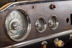 Painel retro do carro do vintage com velocímetro, o tacômetro análogo e o odômetro, os feitos a mão com madeira e cromo para imagem de stock