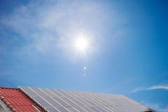 Painel solar e painel da energia solar no céu azul e no sol do telhado vermelho fotografia de stock royalty free