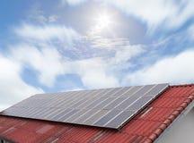 Painel solar e painel da energia solar no céu azul e no sol do telhado vermelho foto de stock