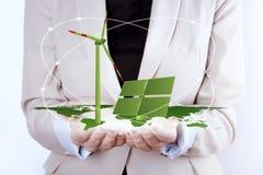 Painel solar e turbina eólica nas mãos das mulheres fotografia de stock royalty free