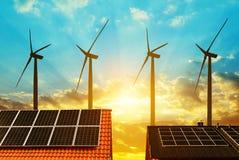 Painel solar no telhado da casa nas turbinas eólicas do fundo no por do sol Foto de Stock Royalty Free