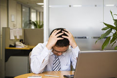 Painful. Young asian businessman facing difficult situation in work Stock Images
