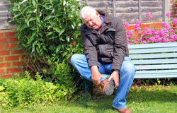 Painful foot, injury or arthritis. A senior man sitting on a bench in agony. He has a pain in his foot caused by an injury or arthritis. Holding his foot and stock photo