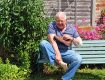 Painful foot, injury or arthritis. A senior man sitting on a bench in agony. He has a pain in his foot caused by an injury or arthritis. Holding his bare foot stock image