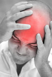 Painful Headache. A young man grips his head in agony.  The red highlighted area illustrates his head pain Royalty Free Stock Images