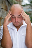 Painful Headache. A stressed out young man grabs his head in annoyance from stress or a headache Royalty Free Stock Photography