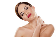Painful neck. Tired young woman stretching her neck and massaging it with her hand Royalty Free Stock Photos