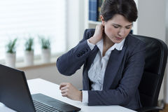 Painful neck. Young working in office woman with painful neck stock photography