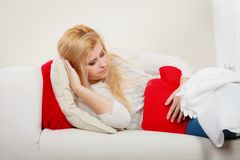 Woman feeling stomach cramps lying on cofa Royalty Free Stock Images
