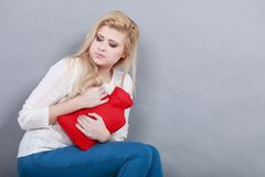 Woman feeling stomach cramps holding hot water bottle. Painful periods and menstrual cramp problems concept. Woman having stomach cramps feeling very unwell Stock Photography