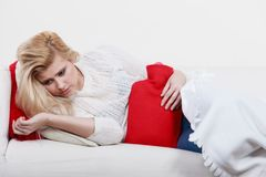 Woman feeling stomach cramps lying on cofa Stock Images