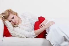 Woman feeling stomach cramps lying on cofa Stock Photography